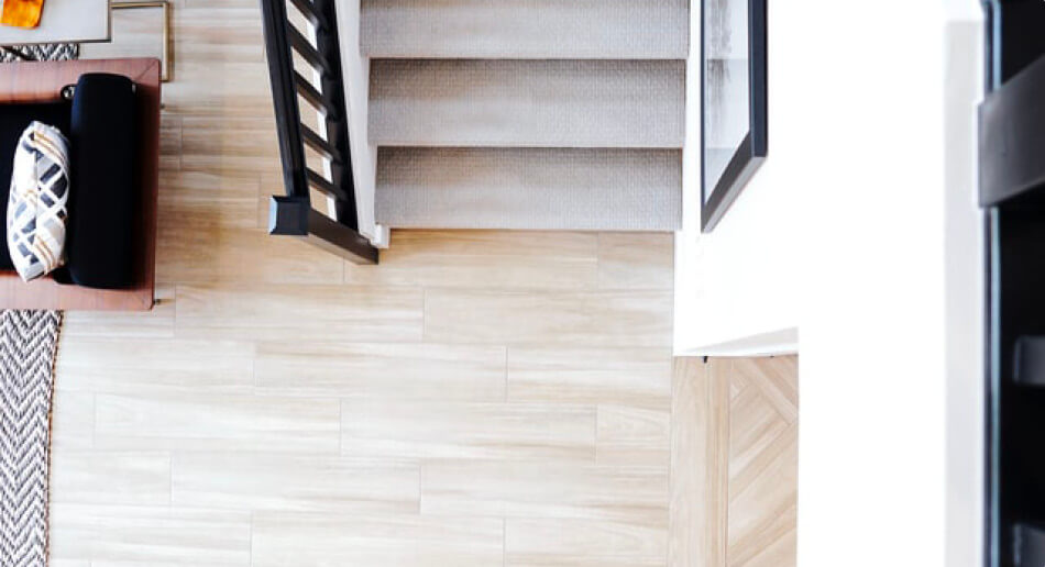 top down image of a light real wood floor and a carpeted stairs