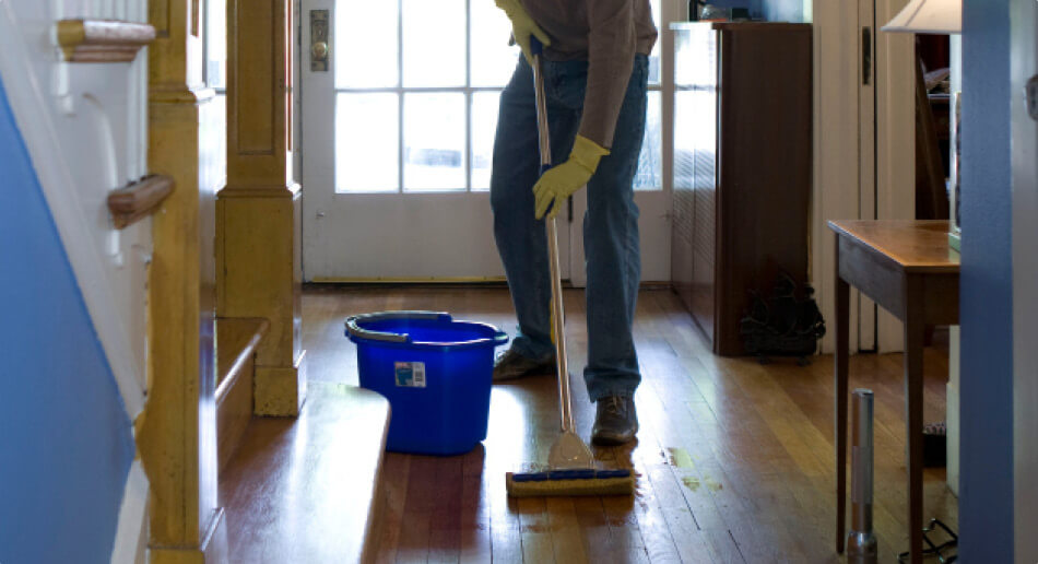Man damp mopping an real wood entrance hallway