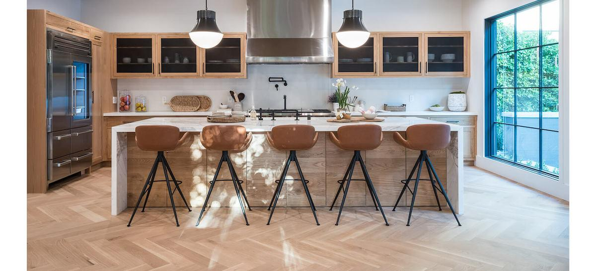 Grand open style kitchen with herringbone style wood flooring