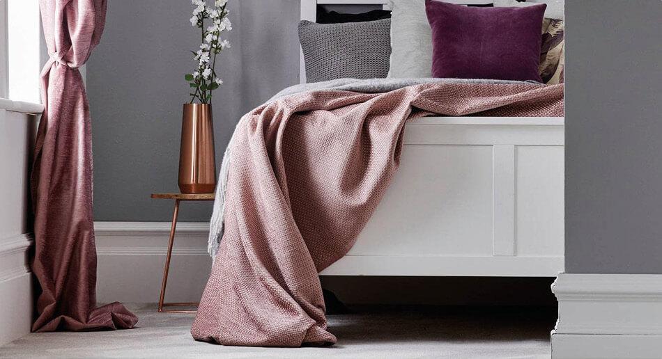 Modern bedroom with grey soft furnishings, dark walls and dark wood floors