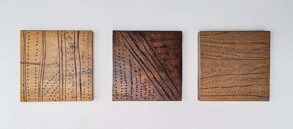 three wood carvings hung up