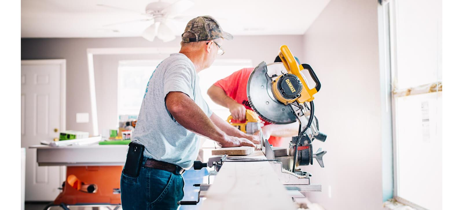 Two men cutting wooden planks using a table saw
